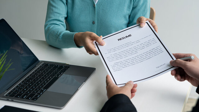 Young applicants who are serious about their work experience. and first impression in a modern office interview The recruiter will consider the resume. The HR manager will consider the employee's resu