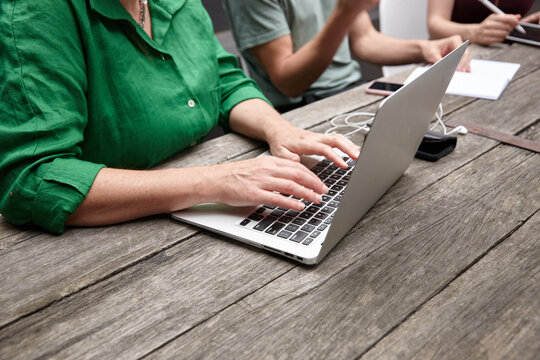 Woman working on laptop outdoors with colleagues