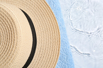 Stylish hat and towel on light background with water splashes, closeup