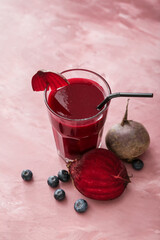 Glass of healthy smoothie with beetroots and blueberries on color background