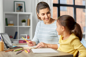 Fototapeta family, motherhood and leisure concept - mother spending time with her little daughter drawing with color pencils at home obraz