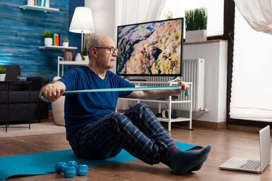 Retirement senior man sitting on yoga mat with leg in crossed position stretching arms muscles using stretch elastic band during sport routine in living room. Pensioner exercising bodyresistance