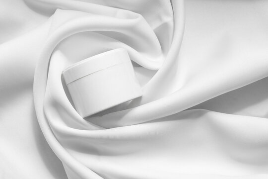 Top view of white jar for packaging cosmetic products, in soft tissue folds. Close-up, monochrome background. Concept of beauty industry