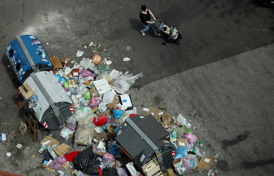 A woman pushes a stroller with a baby inside along piles of garbage lying in front of rubbish bins in Rome