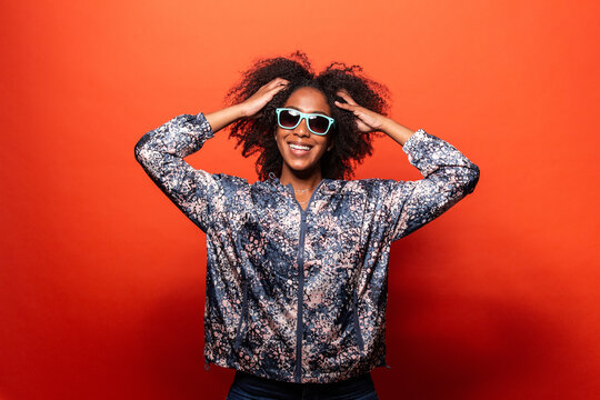 Stylish black woman in sunglasses against red background