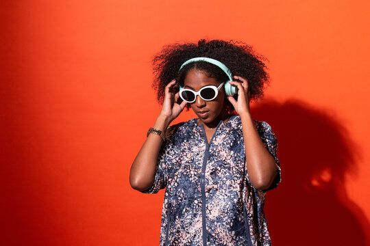 Happy black woman listening to good music in headphones