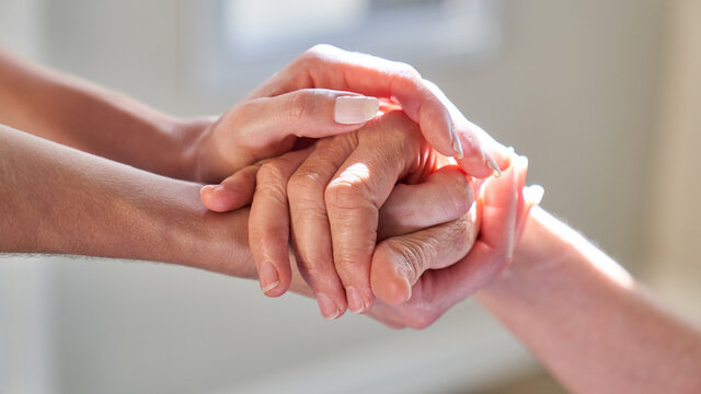 Hands held by senior woman for assistance in hospice