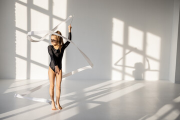 Little girl practising rhythmic gymnastics with a gymnastic tape at white sunny dance room. Wide view with copy space and shadows on the background