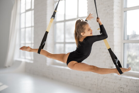 Little girl stretching on suspension straps, doing twine while practicing gymnastics at gym