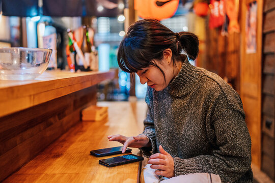 Young woman browsing smartphone in cafe