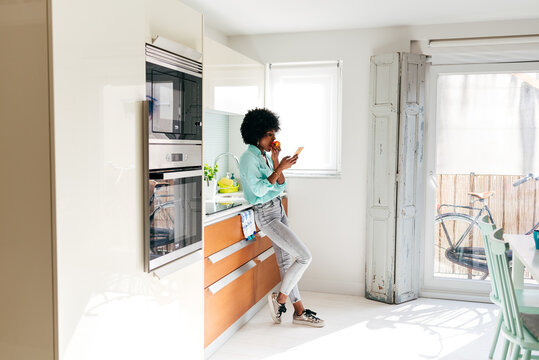 Woman eating fruit and browsing smartphone at home