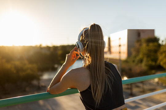 Young woman stretching after working out outdoors at sunset