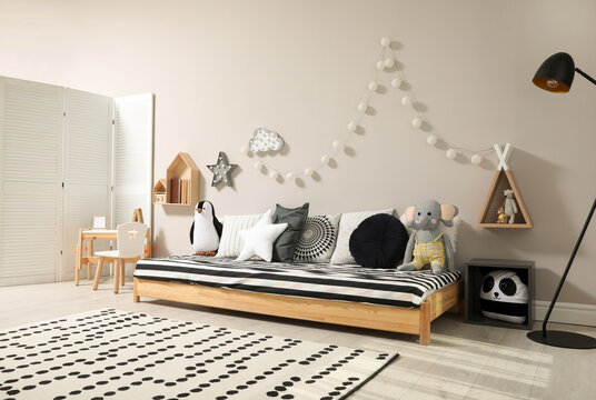 Cute kids room with stylish comfortable floor bed and toys. Montessori interior