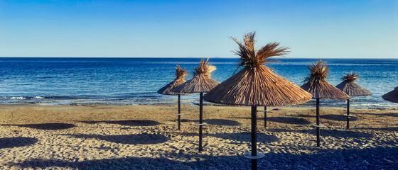 Obraz Parasole plażowe na pustej plaży - fototapety do salonu