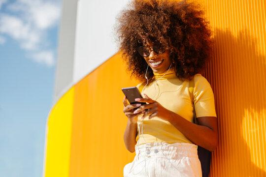 Happy black woman in earphones surfing internet on smartphone outdoors