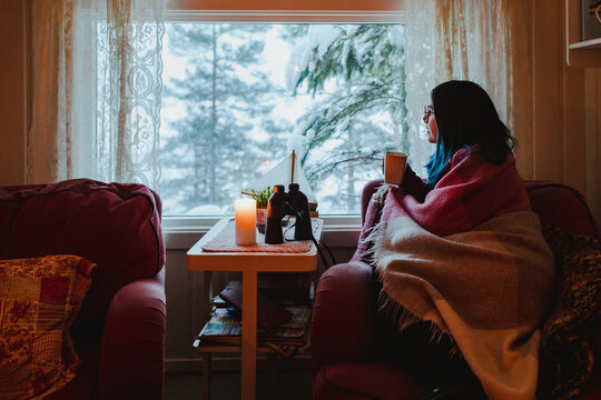 Woman in blanket with cup on sofa near window with view of trees in snow