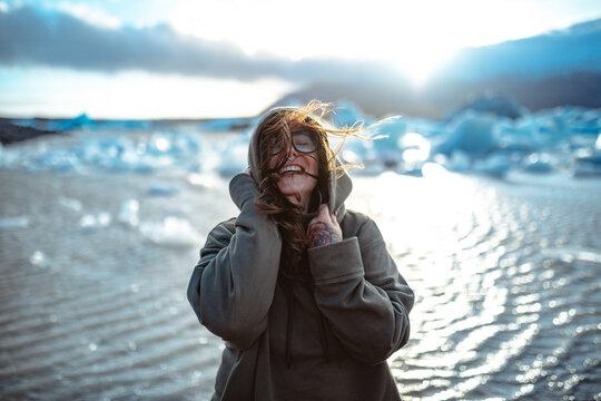 Smiling woman in eyeglasses near water