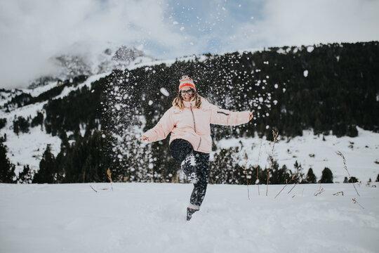 Smiling woman in eyeglasses having fun between wild lands in snow
