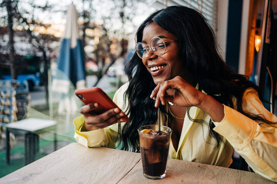 Black woman using smartphone in cafe