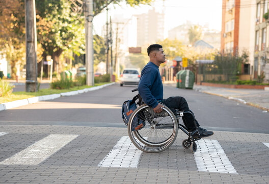 profile of black man with wheelchair crossing the street.
