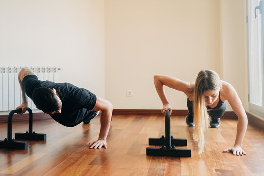 Sporty couple doing push ups with dip stands
