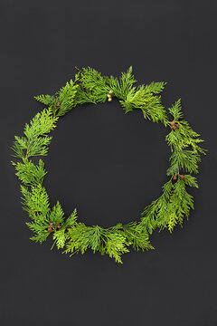 Cedar cypress wreath on dark grey background. Natural composition for Winter solstice, Christmas and New Year.