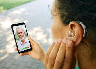 Adult woman with a hearing aid in her ear communicates with her father via video communication via...
