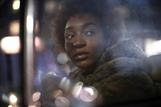 Beautiful young woman looking out car window at night