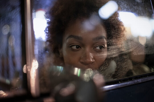 Young woman looking out car window at night