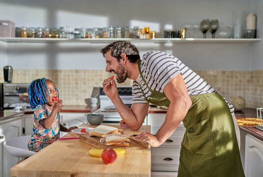 Father and daughter eating at kitchen island