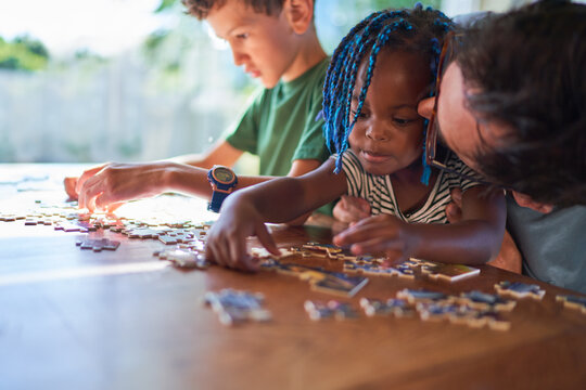 Father kissing cute toddler daughter assembling jigsaw puzzle