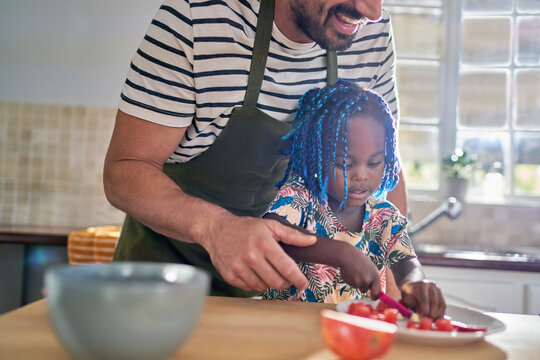 Father helping daughter slice fruit at home
