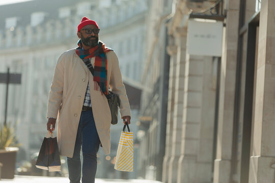 Man with shopping bags walking on sunny city sidewalk