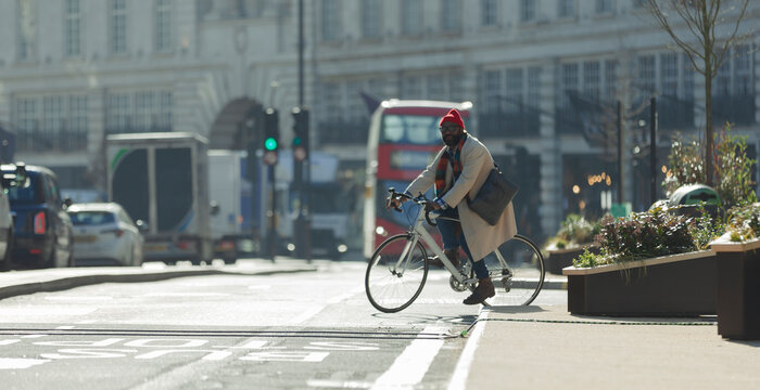 Male commuter riding bicycle on sunny city street, London, UK