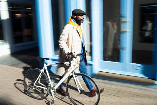 Man walking bicycle along sunny storefront