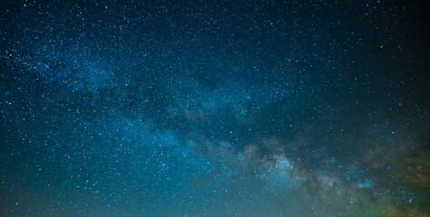 On the starry night sky, the Milky Way. The bright blue colors of the sky and the quiet twinkling of the stars create a fabulous picture. High angle view. Background. Wallpaper.