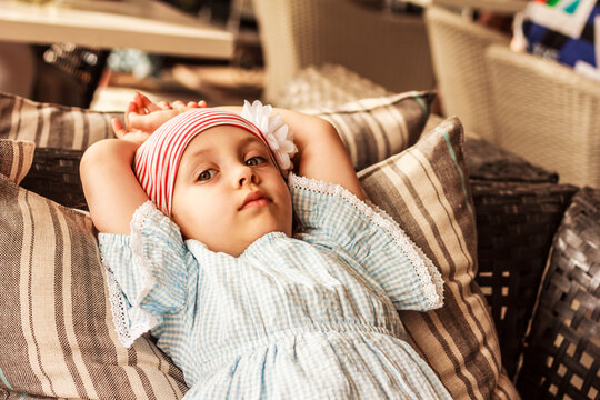 A little girl wearing a light blue summer dress is lying on striped pastel colored cushions  in the armchair or on the bench and looking thoughtfully. Summer Relax concept