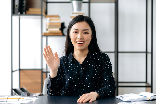 Webcam headshot of a positive pretty, smart confident young asian woman, freelancer or manager, sits at work desk, talking with colleagues or friends via video link, waving hand, smiling friendly