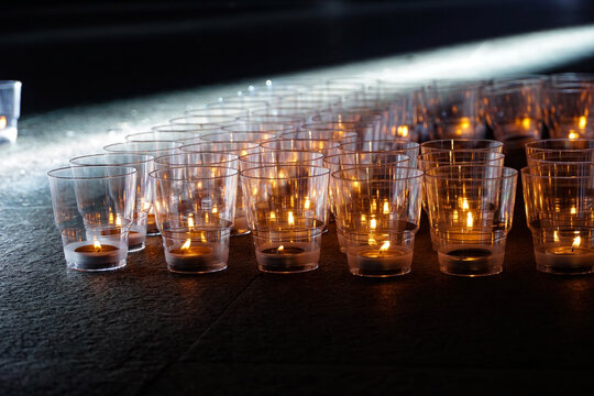 burning candles in transparent plastic cups, memory action, dark background, evening time, live fire, candle flame