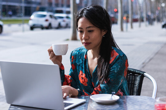Long-haired brunette Asian woman having a coffee on a terrace of a cafe while is working with a laptop
