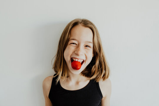 Excited girl eating strawberry and smiling