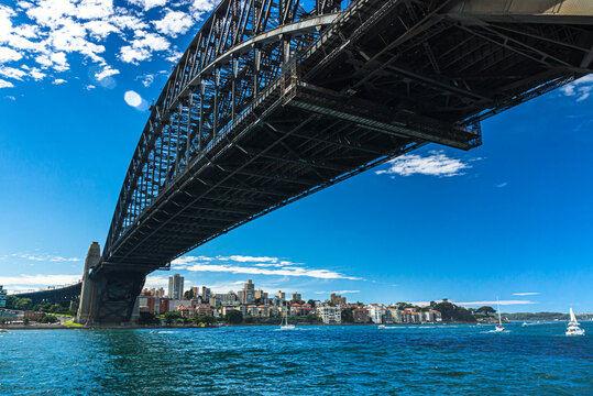Sydney bay with yachts in the water passing under heavy metal bridge.