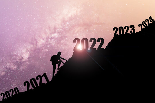 Man climbing mountains and going through and changing 2020 ,2021 to enter 2022. Happy New Year 2022 concept. Happy new year and holiday concept.Success new year concept.