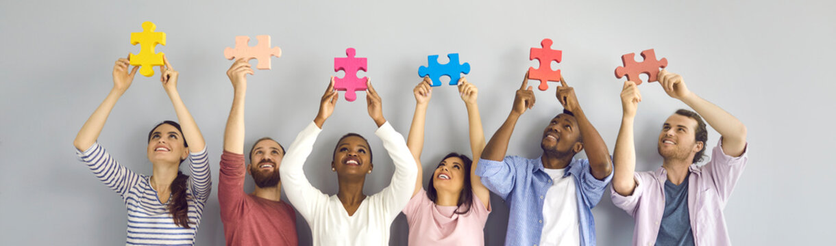 Group of six happy smiling young people holding big colorful jigsaw puzzle pieces standing against light grey studio background. Team of creative millennials cooperate and find good solution together
