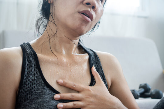 tired Asian woman having heart attack after doing sport hand holding her chest pain that sweat from overtraining