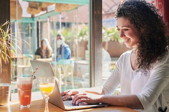 Ethnic distance worker typing on laptop during breakfast in restaurant