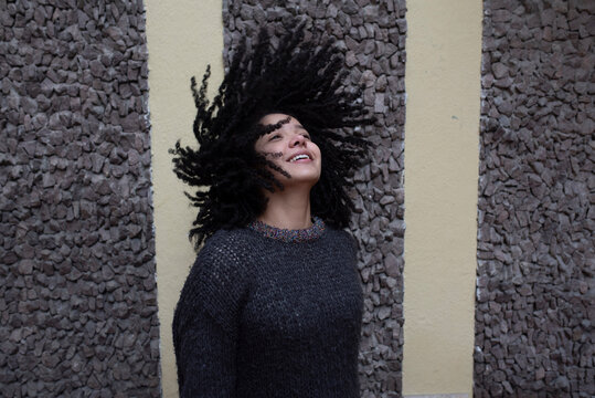 Carefree woman with flying curly hair in street