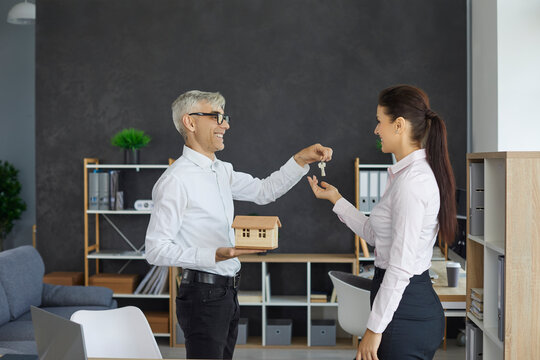 Professional real estate agent gives keys to happy client. Young woman visits realtor's office and takes keys to new home. Buying own house, getting mortgage approval, making dream come true concept