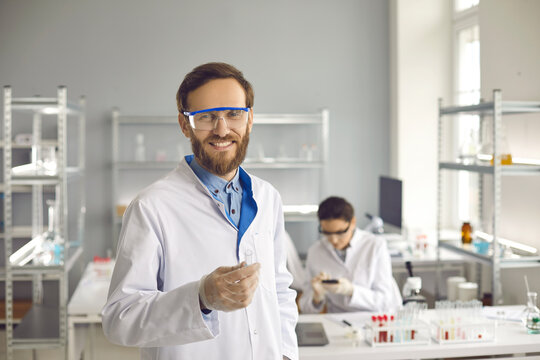 Portrait of a smiling male scientist or doctor standing in a laboratory with a test tube in his hand. Concept of research and experiments in the pharmaceutical industry.