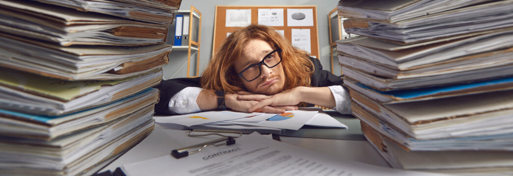 Sad busy clerk looking at too much paperwork. Panorama background banner with tired worker at messy office desk full of disorganized papers, many work contracts and lots of corporate bookkeeping data